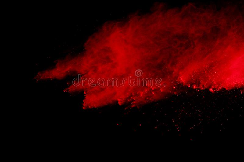 Abstract of red powder explosion on black background. Red powder splatted isolate. Colored cloud. Colored dust explode. Paint Holi.  stock image
