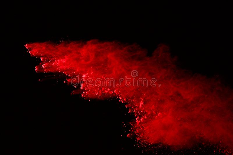 Freeze motion of colored powder explosion isolated on black background. Abstract of Multicolor dust splatted. Abstract of red powder explosion on black royalty free stock photo