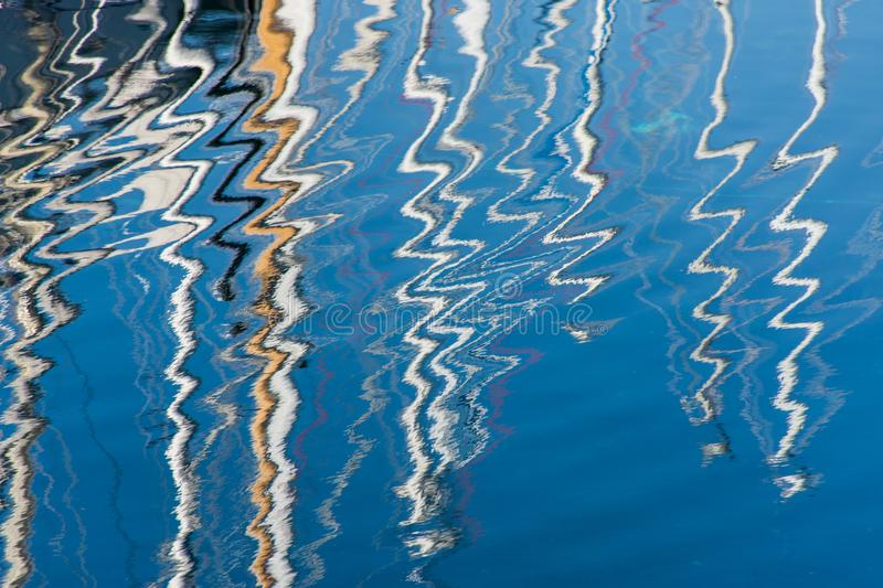 Abstract Reflection of colorful sailboats masts on a rippled water surface stock photos