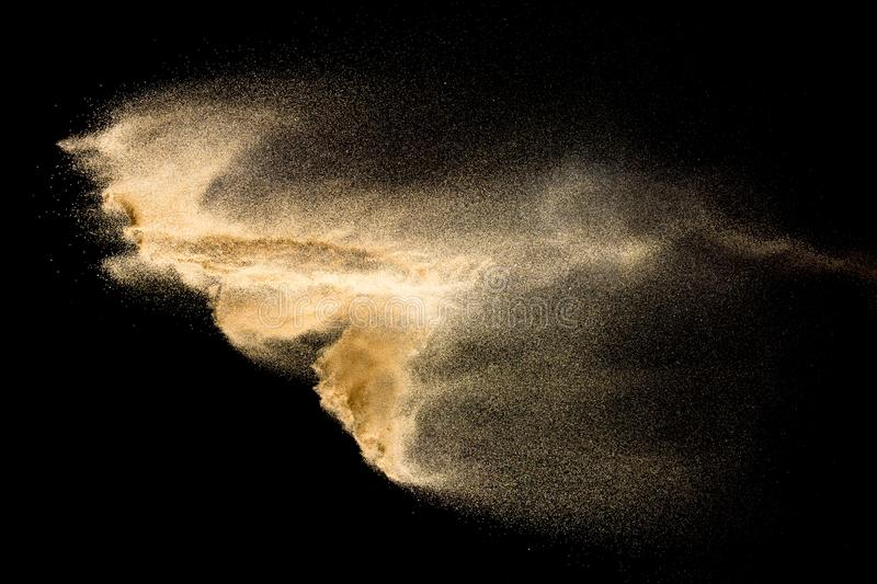 Abstract river sand cloud. Golden colored sand splash against black background. Yellow sand fly wave in the air.  royalty free stock images