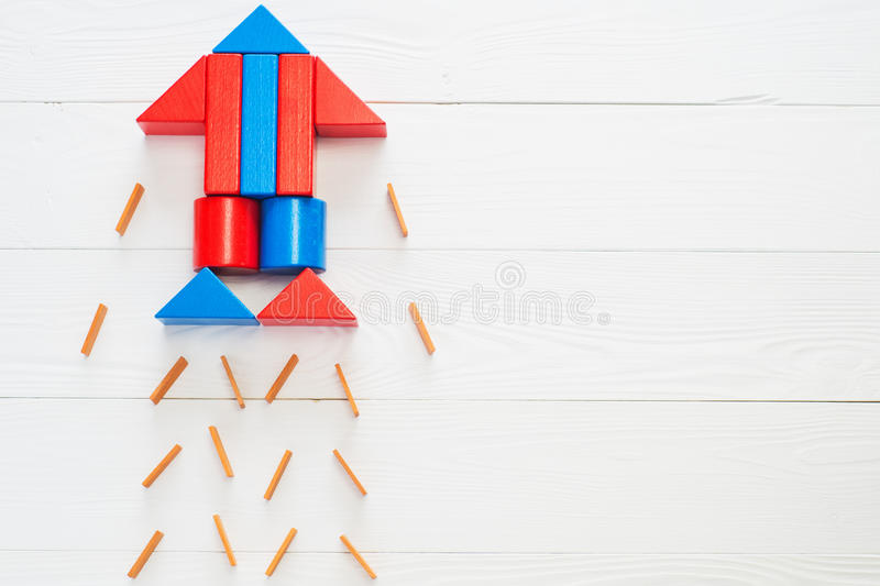 Abstract rocket from colored wooden blocks. On a white wooden background with copy space. Business concept, startup, achievement, success. Wooden puzzle in royalty free stock image