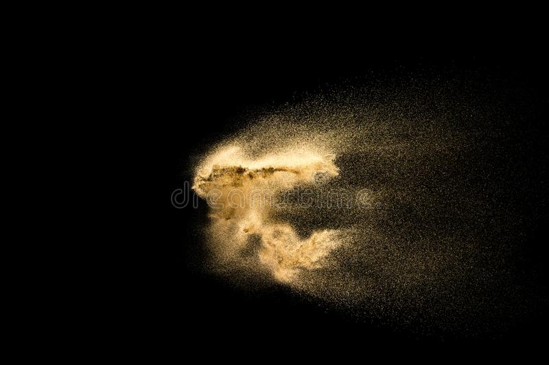 Abstract sand cloud. Golden colored sand splash against dark background. Sandy fly wave in the air royalty free stock image