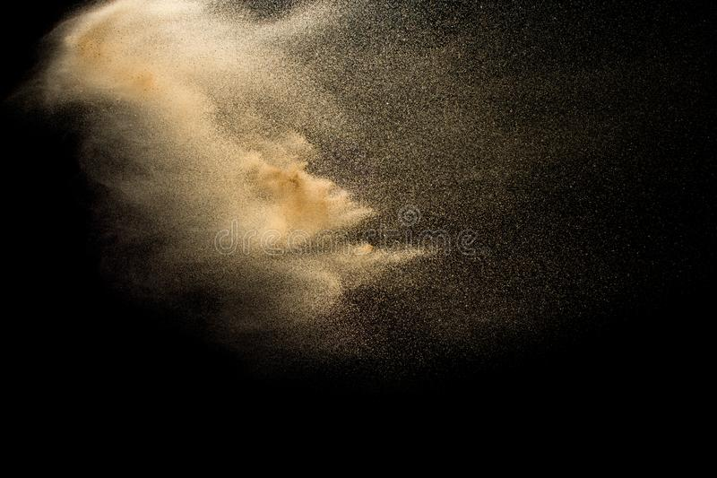 Abstract sand cloud.Golden colored sand splash agianst dark background.Yellow sand fly wave in the air. Sand explode on black background ,throwing freeze stop royalty free stock photography
