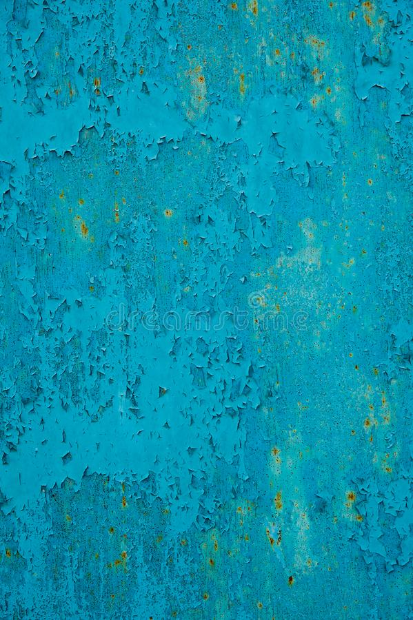Abstract scratched section of an old metal garage door in blue with small spots of rust stock image