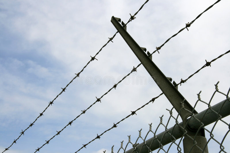 Abstract Security. Detail of the barbed wire fence surrounding a secure compound stock images