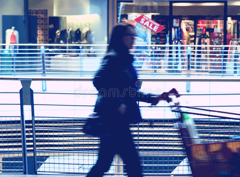 Abstract shopping. Composition with woman and shopping cart in commercial center during sales season