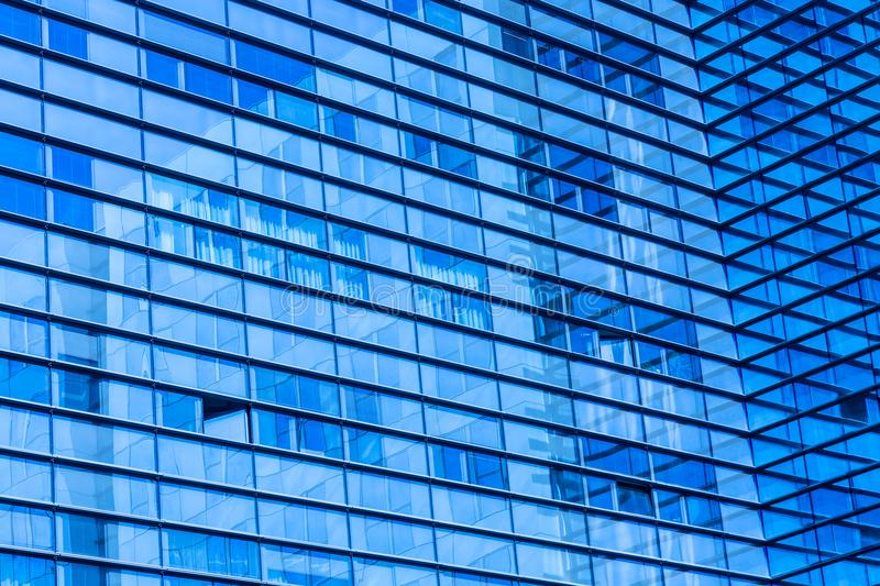 Abstract shot of glass transparent skyscraper office building for texture or background. Blue toned. royalty free stock image
