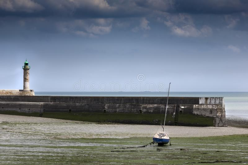 Abstract shot in low tide with a small fishing boat and concrete stock images