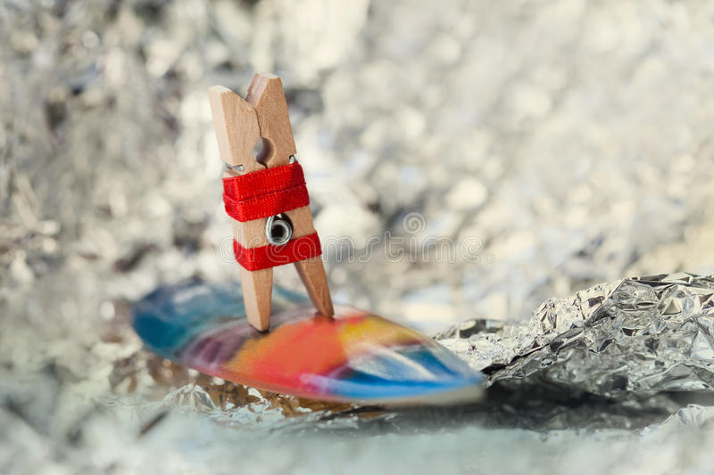 Abstract sport concept with surfing clothespin. Surfer girl on a wave stock photography