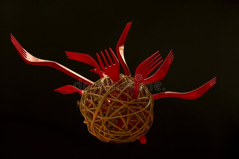 Abstract still life with red forks in a round empty ball made of tree branches.  royalty free stock image