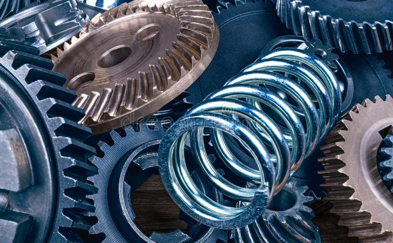 Steel coil spring and various gearwheels close-up. Abstract technical background from a pile of blue and silvery metal parts. Beautiful texture from cogged royalty free stock image
