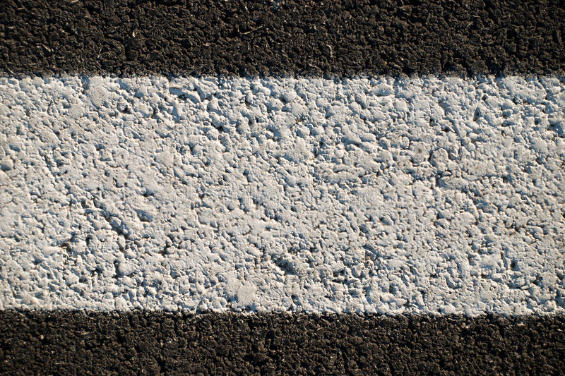Abstract texture of a asphalt road with white paint stock image