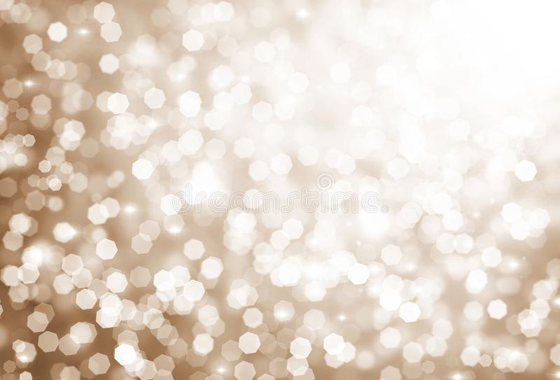 Blurred bokeh background, white circles on gold background, glitter, glow stock image