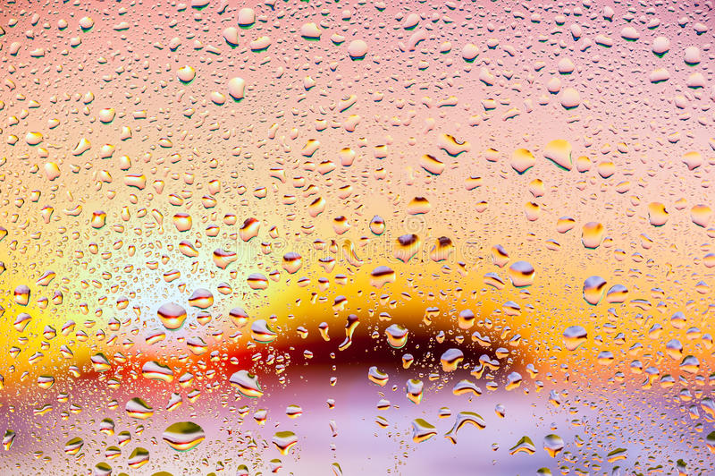 Abstract texture. Water drops on glass with nice sunset background royalty free stock photography