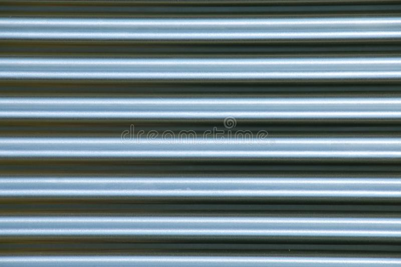 Close up of a silver corrugated metal sheet. Abstract textured background of close up detail of a sheet of silver corrugated metal stock images