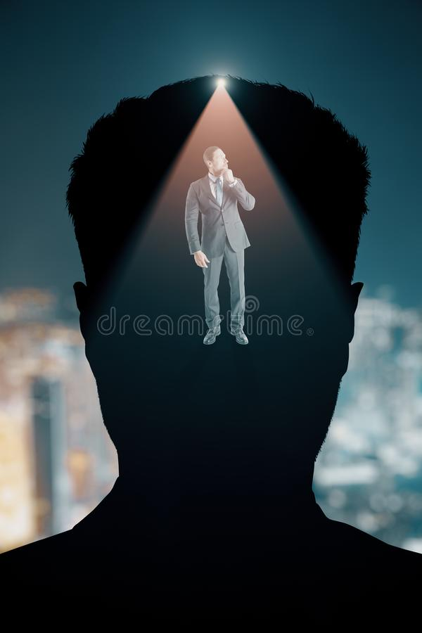 Abstract thoughtful businessman. Abstract portrait silhouette and thoughtful businessman on blurry night city background. Thoughts concept. Double exposure stock image