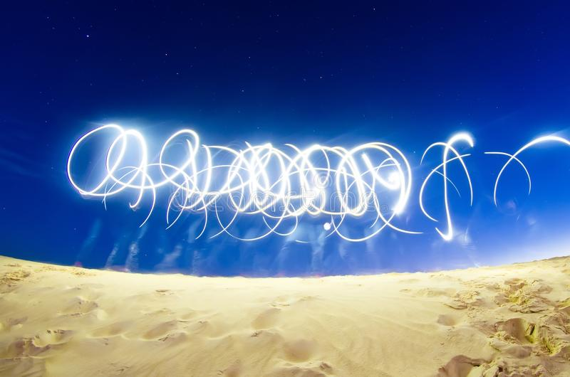 Abstract traces from the light of phone flashlights in the empty on the starry sky. stock photography