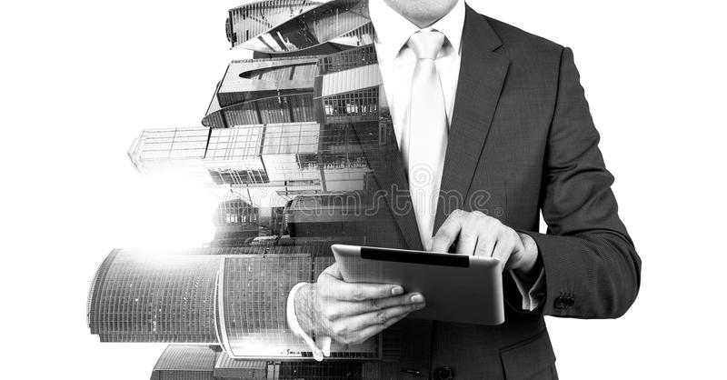 An abstract transparent businessman is looking something in the tablet. Moscow city business centre view. royalty free stock photography