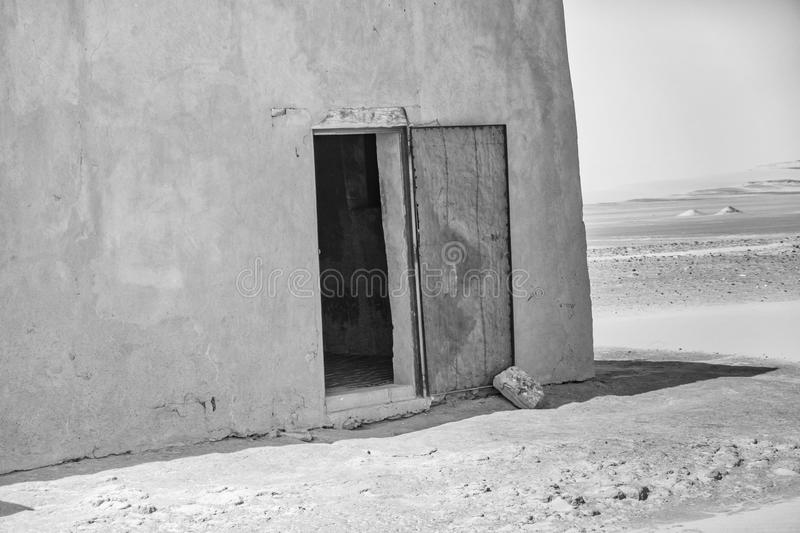 Abstract unreal picture of the corner of a house in the desert with an open blue damaged door of iron, Sudan. Abstract unreal black-and-white picture of the royalty free stock image