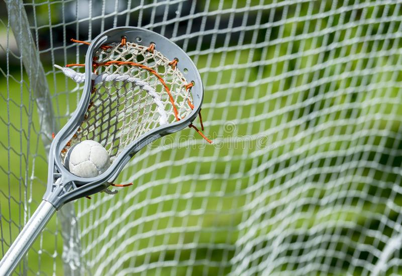 Abstract view of a lacrosse stick scooping up a ball stock photo