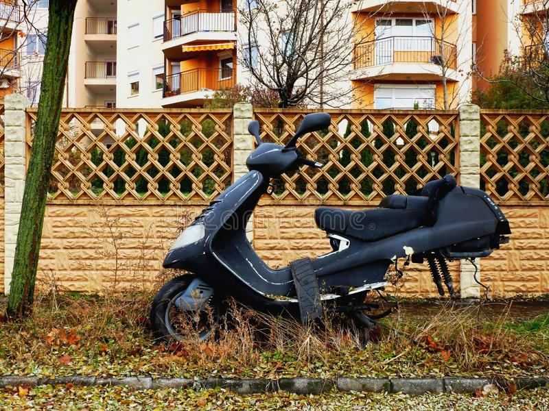 Old wrecked scooter parked on street with parts missing stock photo