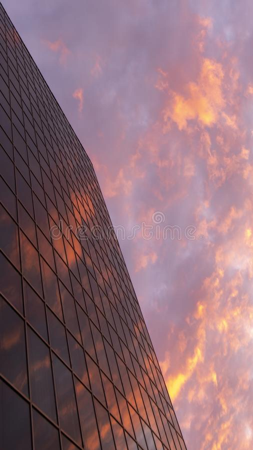 Abstract view of a skyscraper with a reflection of the evening sky and red clouds. Copy space. Beautiful geometric city view. stock image