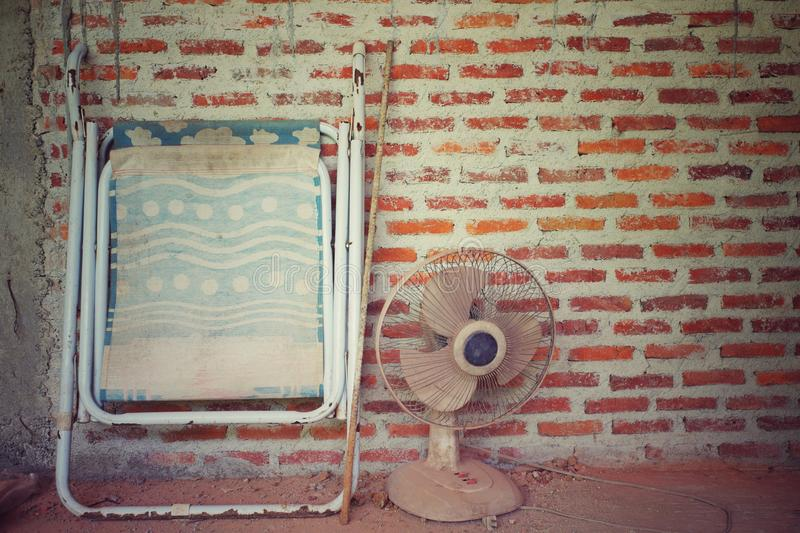 Abstract vintage picture of dirty folding bed and electrical fan with brickwork wall in background. At the construction site. Take a break in the site stock photos
