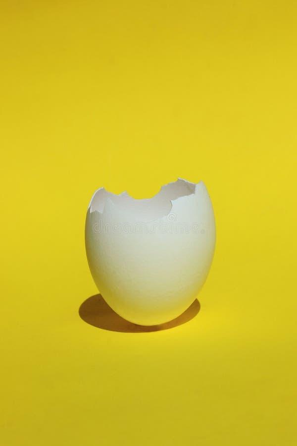 Abstract Voedselingredi?nt Gebarsten ei dicht omhoog Gebroken Witte Kippeneierschaal Witte Eierschaal over Gele Achtergrond stock foto's