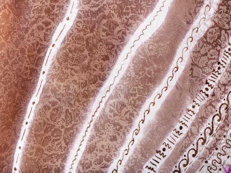 Abstract white and brown striped ornament on batik. Textile background - abstract hand painted white and brown striped ornament on silk batik royalty free stock images