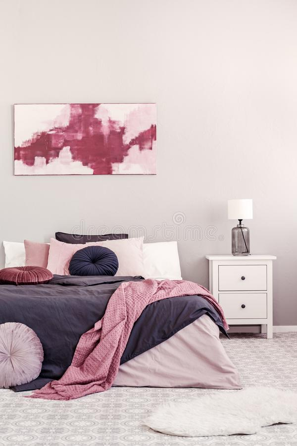Abstract white and burgundy painting on the wall of stylish bedroom interior with king size bed stock photography