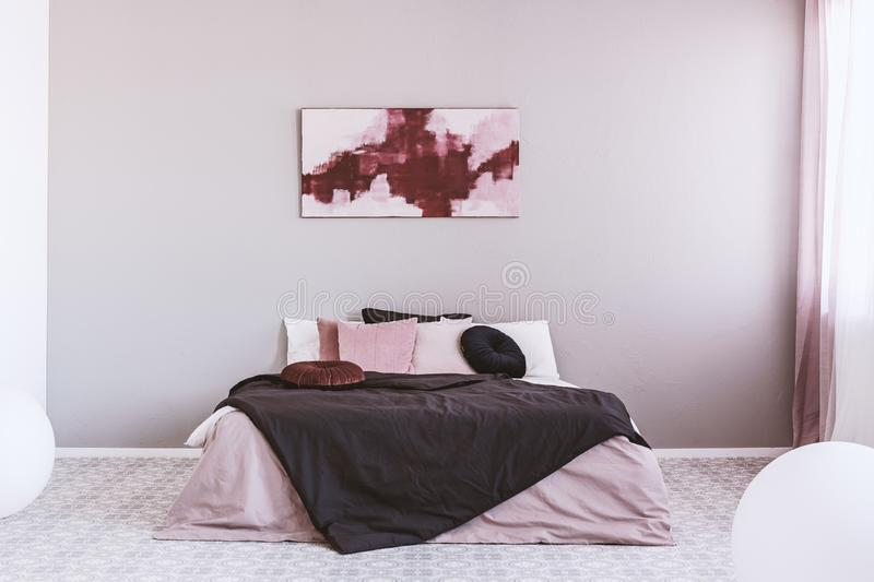 Abstract white and burgundy painting on the wall of stylish bedroom interior with king size bed stock photos