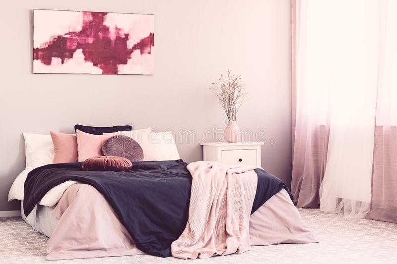 Abstract white and burgundy painting on the wall of stylish bedroom interior with king size bed stock photo