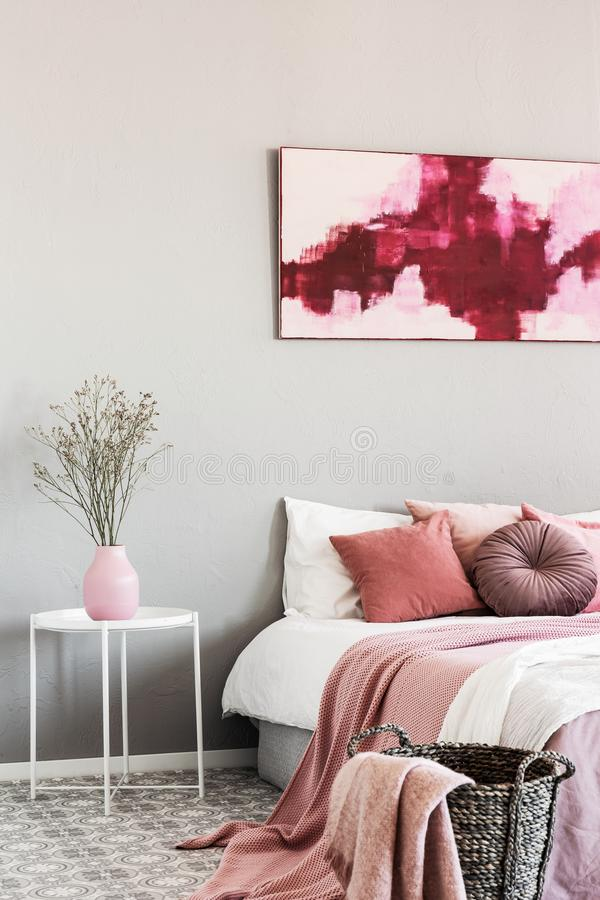Abstract white and burgundy painting on the wall of stylish bedroom interior with king size bed royalty free stock images