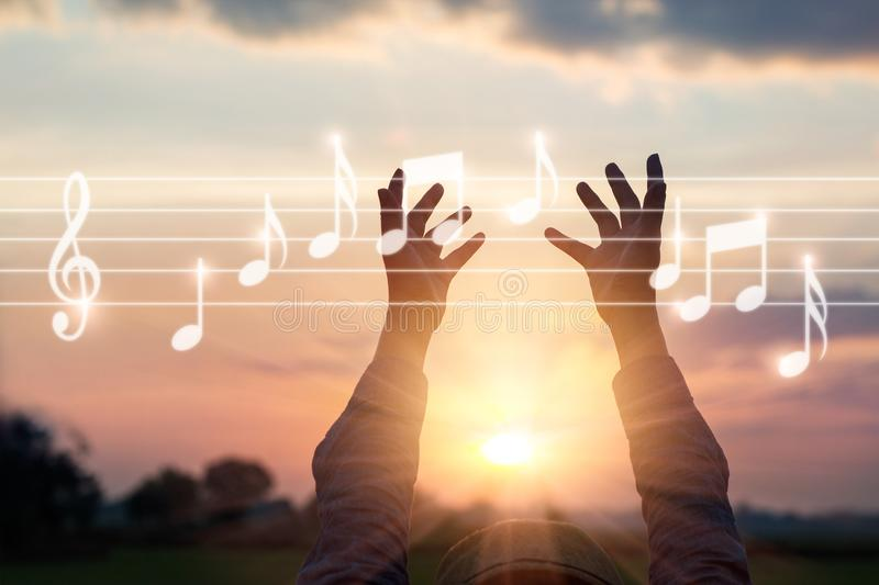 Abstract woman hands touching music notes on nature background, royalty free stock photo