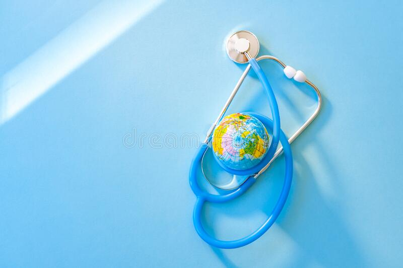 Abstract World Health Day concept with stethoscope and globe on blue background. Copy space. Healthcare stock photo