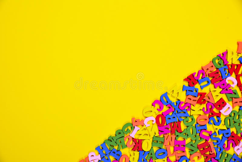Abstract yellow background with multicolored letters. Of the English alphabet, blank space on the left royalty free stock photos