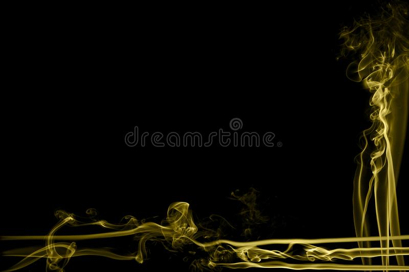 Abstract yellow colored smoke flowed on black background. stock photos
