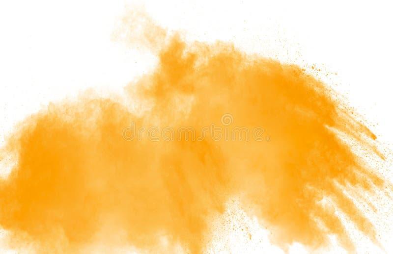 Abstract yellow orange powder explosion on white background. Freeze motion of orange  dust particles splash.  royalty free stock image