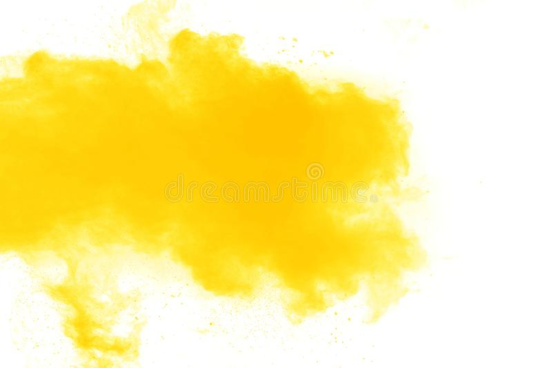 Abstract yellow orange powder explosion on white background. Freeze motion of yellow dust particles splash.  stock image