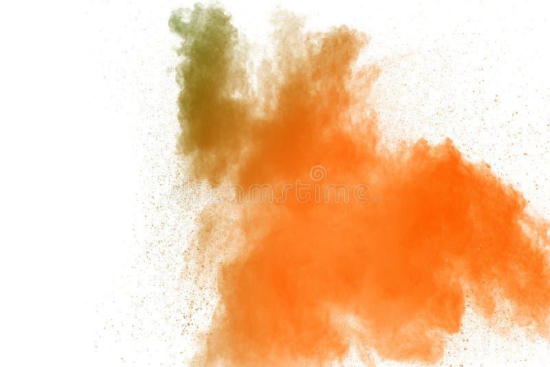 Abstract yellow orange powder explosion on white background. Freeze motion of yellow orange dust particles splash.  royalty free stock photo