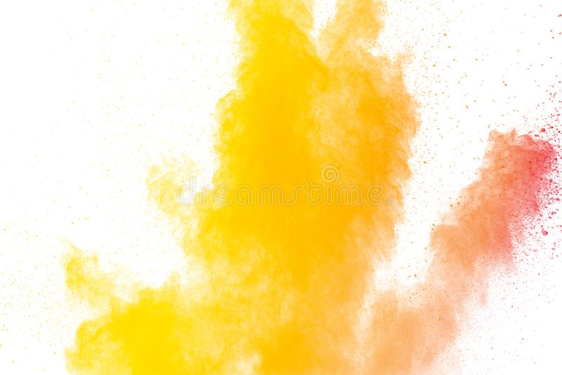 Abstract yellow orange powder explosion on white background. Freeze motion of yellow orange dust particles splash.  stock photo