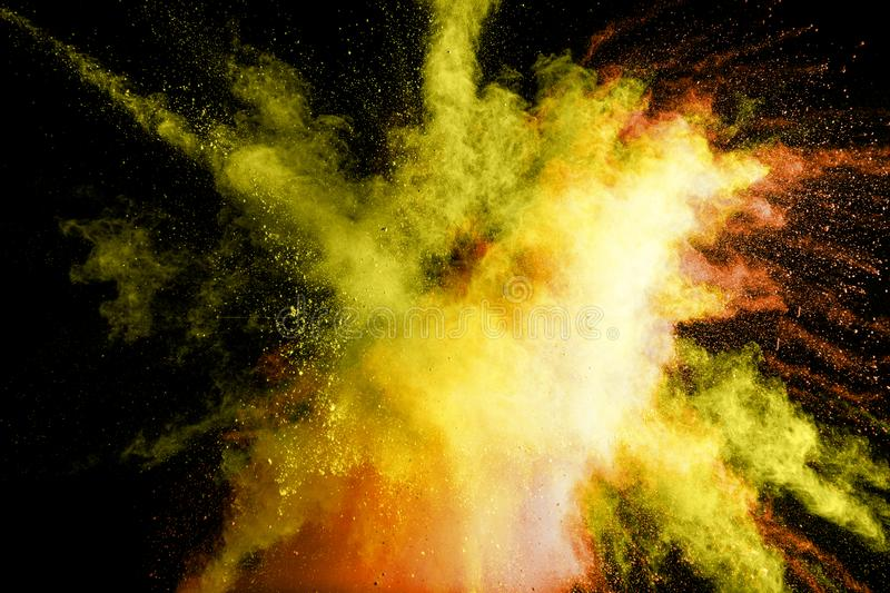 Abstract yellow powder explosion on black background.Freeze motion of yellow dust splash.  royalty free stock photo