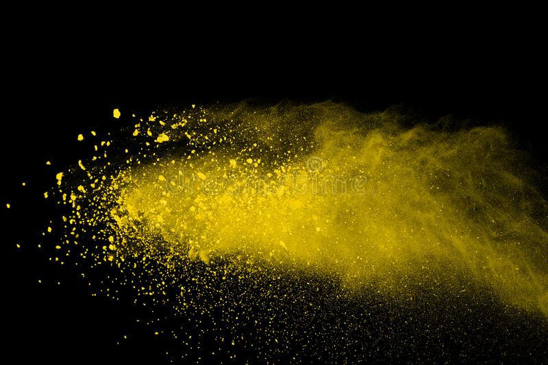 Abstract of yellow powder explosion on black background. Yellow powder splatted isolate. Colored cloud. Colored dust explode. Pain stock photos