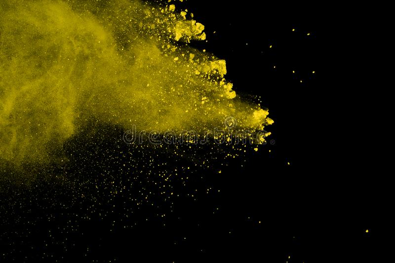 Abstract of yellow powder explosion on black background. Yellow powder splatted isolate. Colored cloud. Colored dust explode. Pain royalty free stock images
