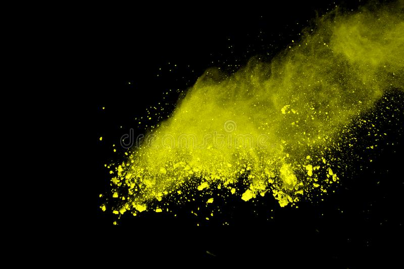 Explosion of colored powder, isolated on white background. Abstract of colored dust splatted. Color cloud. Abstract of yellow powder explosion on black stock image