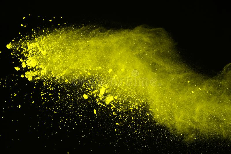 Freeze motion of colored powder explosion isolated on black background. Abstract of Multicolor dust splatted. Abstract of yellow powder explosion on black royalty free stock images