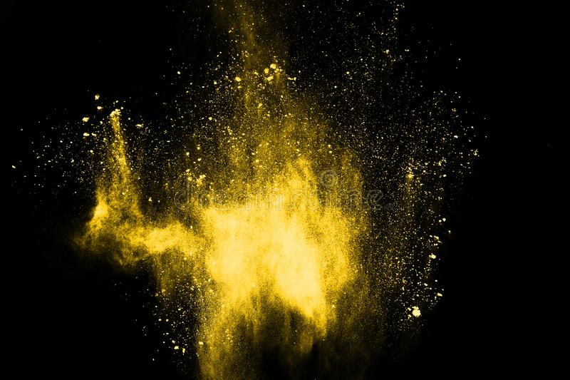 Freeze motion of yellow dust explosion isolated on black background. royalty free stock photo