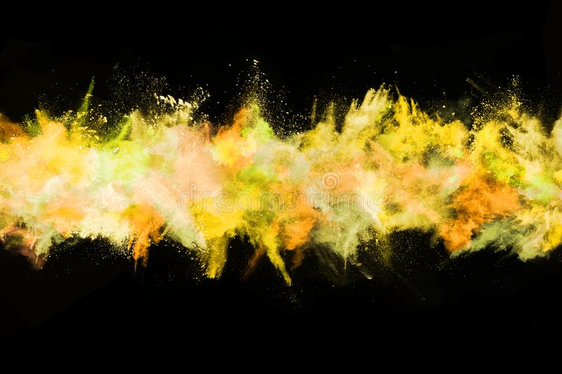 Yellow color powder explosion on black background royalty free stock photo