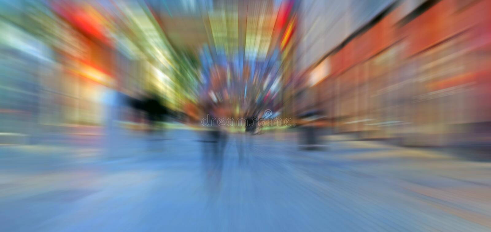Abstract zoom blur of a modern city street at night with people walking and bright illuminated buildings stock photos