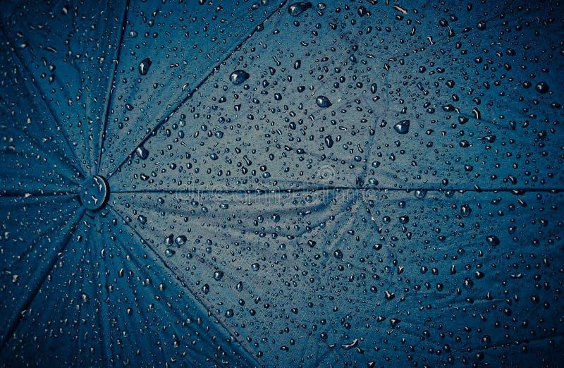 Abstracte achtergrond, blauwe paraplu met regendruppels stock afbeeldingen